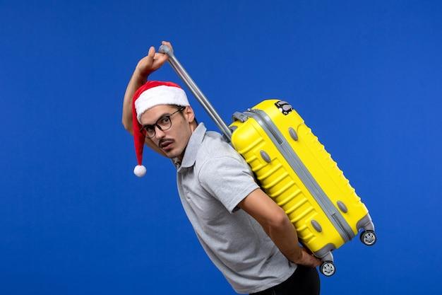 Jovem masculino carregando uma bolsa pesada em um avião de férias com a parede azul