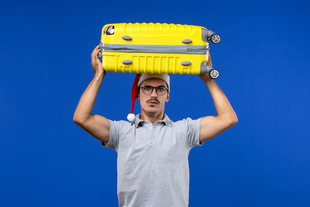Jovem masculino carregando uma bolsa pesada na parede azul voos de férias