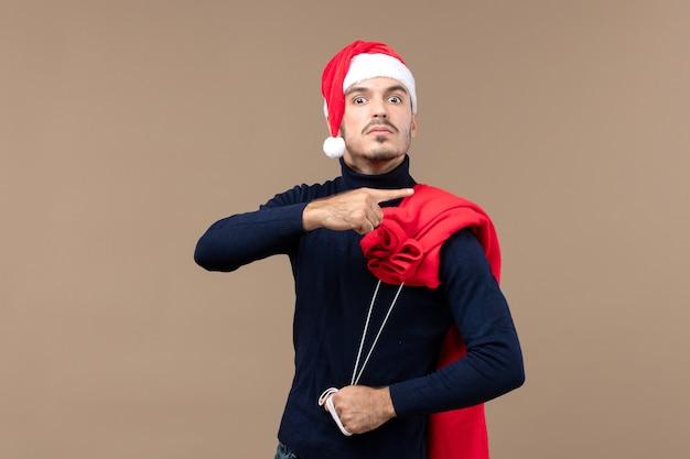 Jovem masculino carregando uma sacola de presentes no fundo marrom natal feriado papai noel