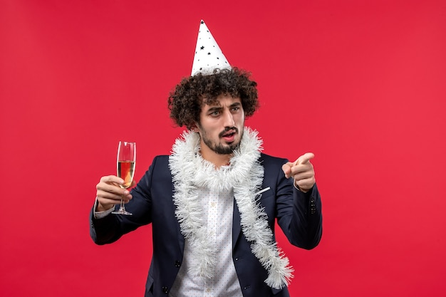 Jovem masculino celebrando o ano novo chegando na parede vermelha festa natalina
