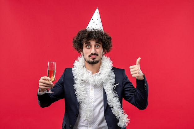 Jovem masculino celebrando o ano novo na mesa vermelha, festa natalina
