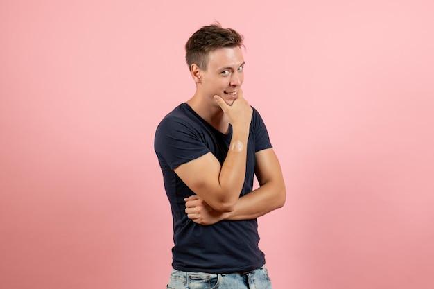 Jovem masculino com camisa azul escura posando com um sorriso no rosto rosa claro