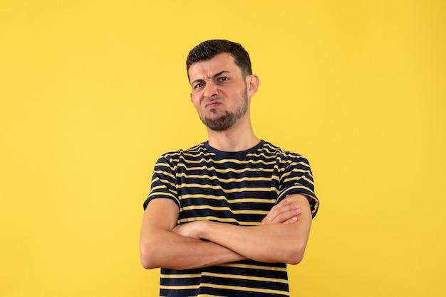 Jovem masculino com camiseta listrada em preto e branco, cruzando as mãos em um fundo amarelo isolado