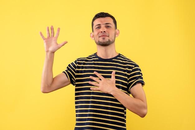 Jovem masculino com camiseta listrada em preto e branco fazendo sinal de promessa em fundo amarelo isolado de frente