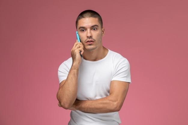Jovem masculino de camisa branca falando ao telefone com uma expressão perturbada no fundo rosa.