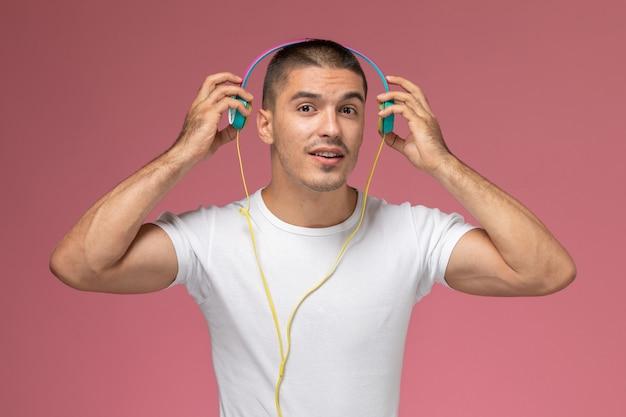 Jovem masculino de camiseta branca ouvindo música com fones de ouvido no fundo rosa