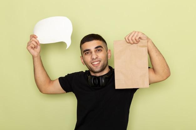 Jovem masculino de camiseta preta segurando uma placa branca e um pacote de comida verde