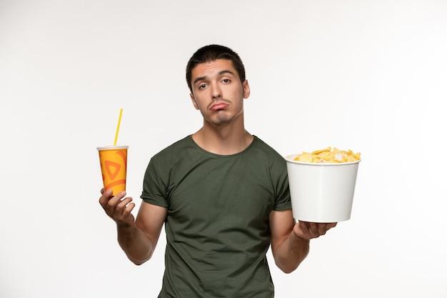 Jovem masculino de camiseta verde segurando batata cips e refrigerante na parede branca filme cinema solitário filmes masculinos de frente