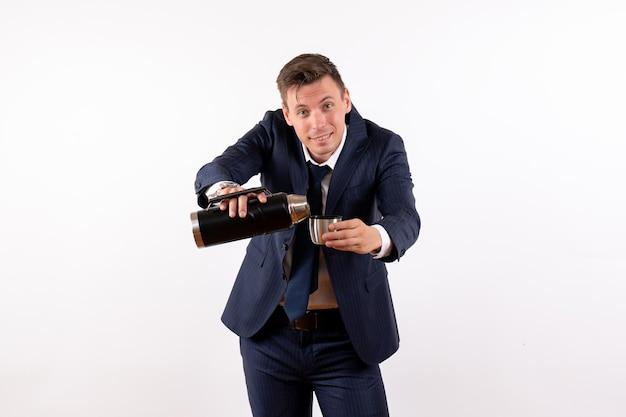 Jovem masculino despejando água da garrafa térmica em um terno clássico na mesa branca