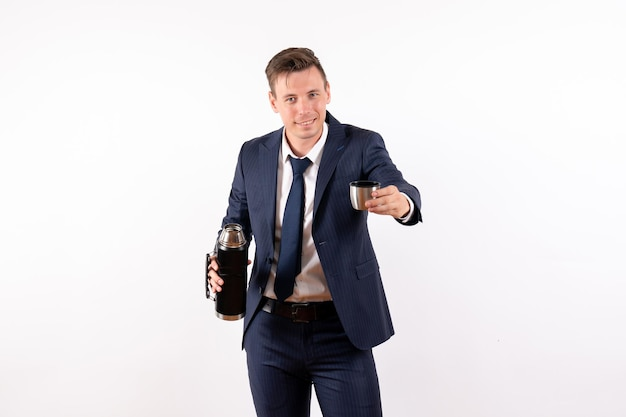 Jovem masculino despejando água da garrafa térmica em um terno clássico sobre fundo branco.