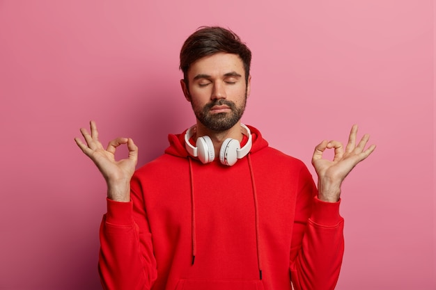 Jovem masculino faz gestos mudra zen, mantém os olhos fechados, usa fones de ouvido no pescoço, medita e respira profundamente, ouve música relaxante, usa um moletom vermelho, posa sobre uma parede rosada