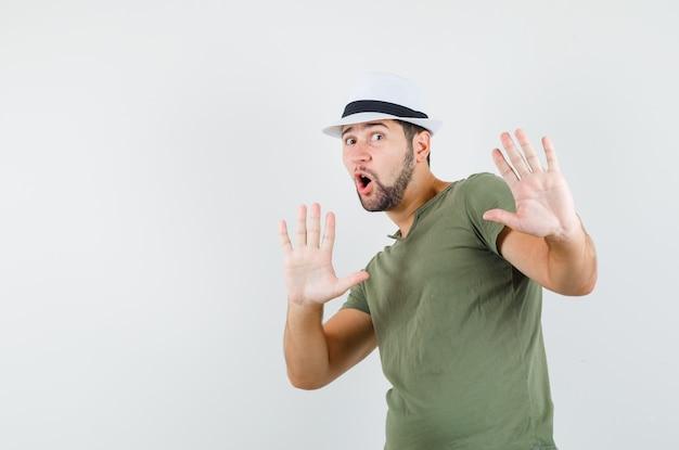 Jovem masculino levantando as mãos de forma preventiva com camiseta e chapéu verdes e parecendo assustado