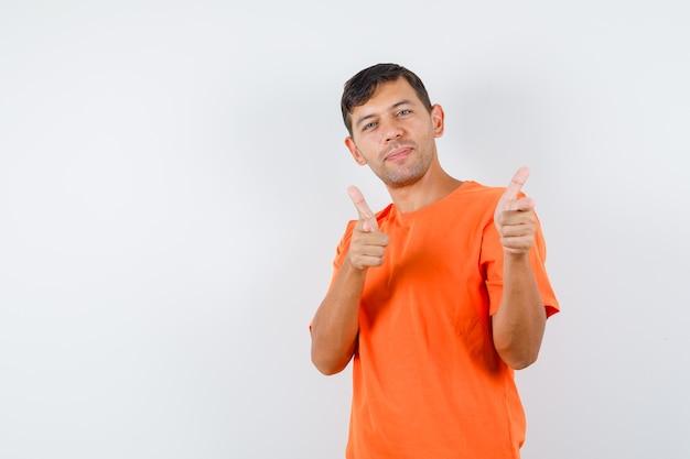 Jovem masculino mostrando gesto de arma apontado para a câmera em uma camiseta laranja e olhando feliz