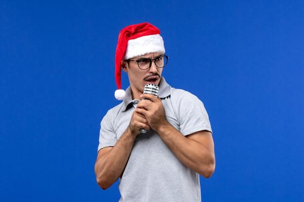 Jovem masculino segurando o microfone na parede azul cantores de ano novo