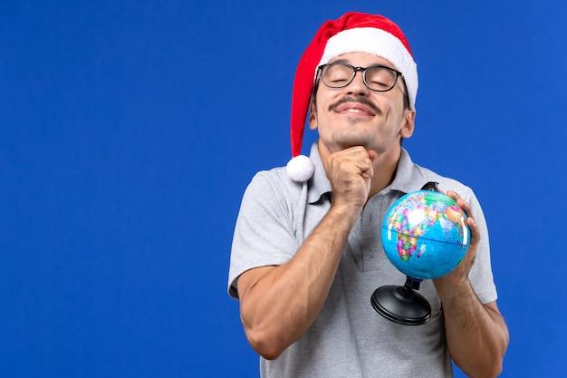 Jovem masculino segurando um globo terrestre na parede azul, viagem avião, férias masculino