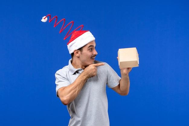 Jovem masculino segurando um pacote de entrega de comida na parede azul do serviço masculino de comida de frente