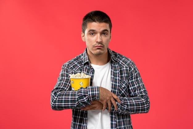 Jovem masculino segurando um pacote de pipoca com expressão estressada na parede vermelha clara.