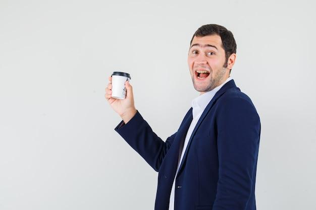 Jovem masculino segurando uma xícara de café com uma camisa, jaqueta e parecendo feliz