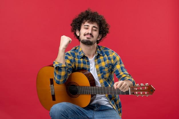 Jovem masculino sentado com a guitarra na parede vermelha. aplausos da banda vermelha.