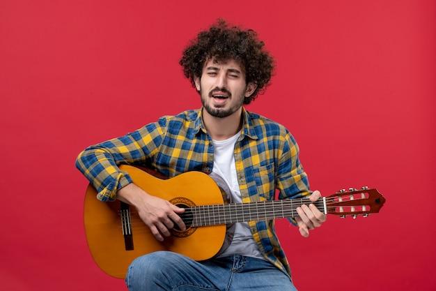 Jovem masculino sentado e tocando guitarra na parede vermelha concerto ao vivo músico aplauso banda toca música