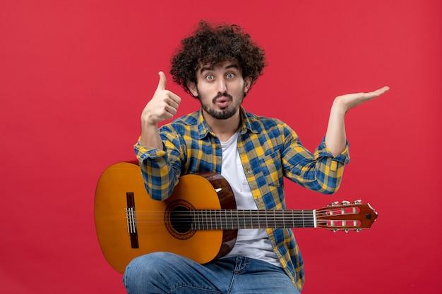 Jovem masculino sentado e tocando guitarra na parede vermelha, concerto ao vivo, músico aplausos, banda tocam cores musicais