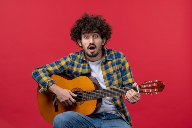Jovem masculino sentado e tocando guitarra na parede vermelha concerto de cor ao vivo música de banda tocam aplausos de frente