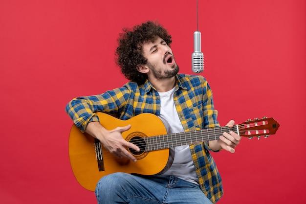 Jovem masculino tocando violão e cantando em uma parede vermelha.