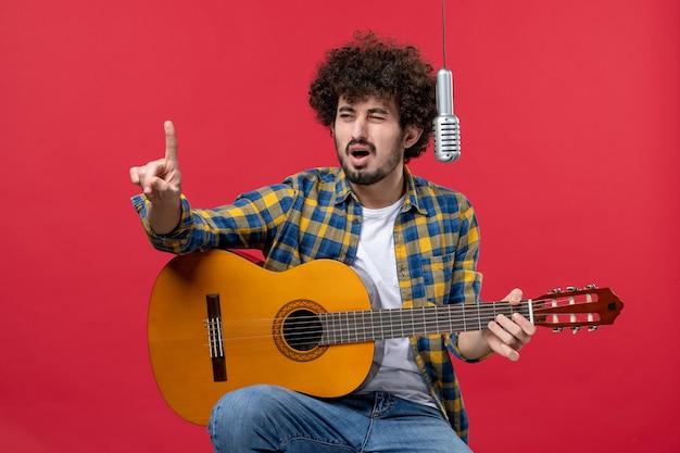 Jovem masculino tocando violão e cantando na mesa vermelha.
