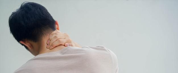 Jovem massagem no pescoço para aliviar os sintomas da dor no pescoço
