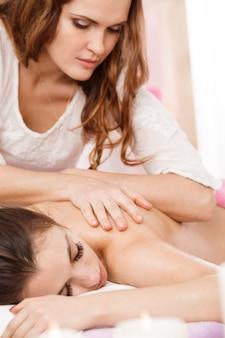 Jovem massagista fazendo massagem nas costas com cuidado. olhando para baixo concentrado