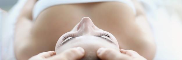 Jovem massagista fazendo massagem no rosto e na cabeça em salão de spa