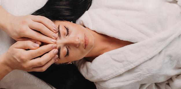 Jovem massagista fazendo uma sessão de massagem facial com uma mulher morena deitada no sofá