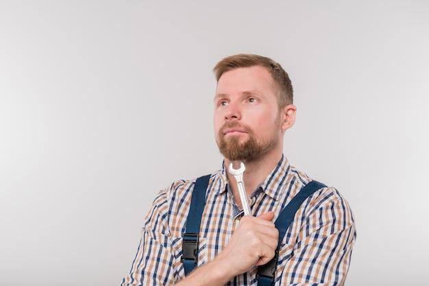 Jovem mecânico barbudo pensativo de macacão e camisa segurando uma chave inglesa pelo queixo enquanto fica de pé isolado contra um fundo preto