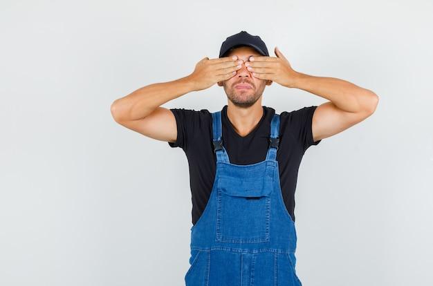 Jovem mecânico cobrindo os olhos com as mãos em vista frontal uniforme.