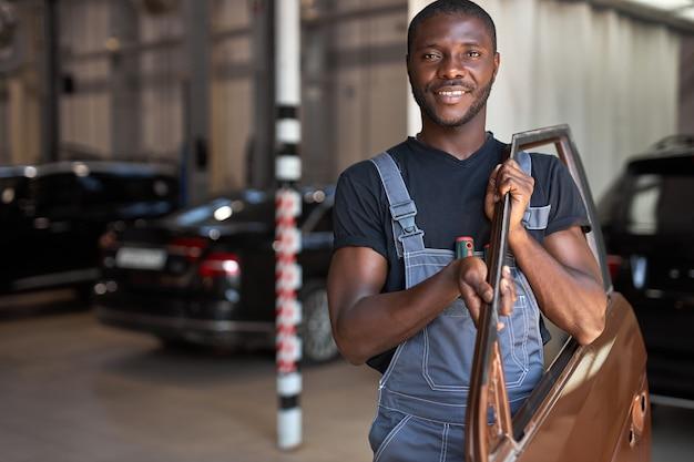 Jovem mecânico de automóveis africano trabalhando com uma parte separada da máquina