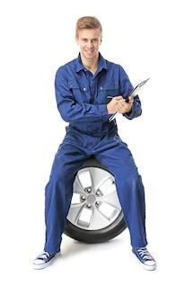 Jovem mecânico de uniforme com uma prancheta em branco