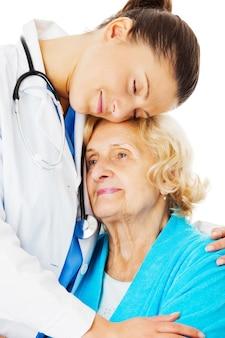 Jovem médica abraçando mulher idosa isolada sobre fundo branco