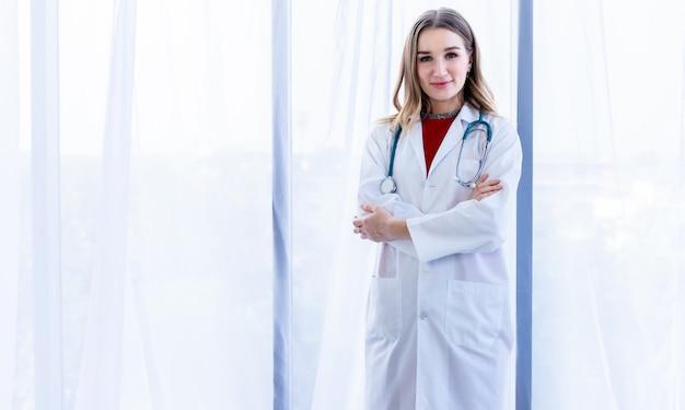 Jovem médica, aconselhamento terapêutico com emoções positivas, com os braços cruzados no fundo do hospital, copie o espaço