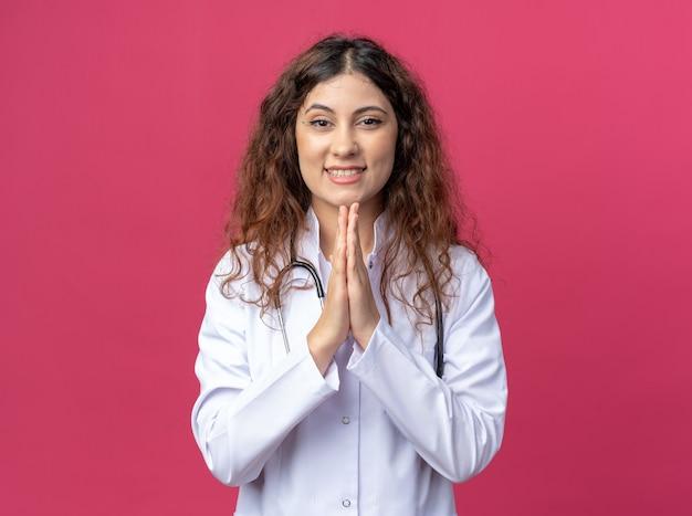 Jovem médica alegre vestindo túnica médica e estetoscópio, mantendo as mãos em gesto de orar, olhando para frente, isolada na parede rosa com espaço de cópia