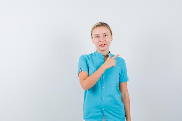 Jovem médica apontando para o canto superior direito com uniforme médico