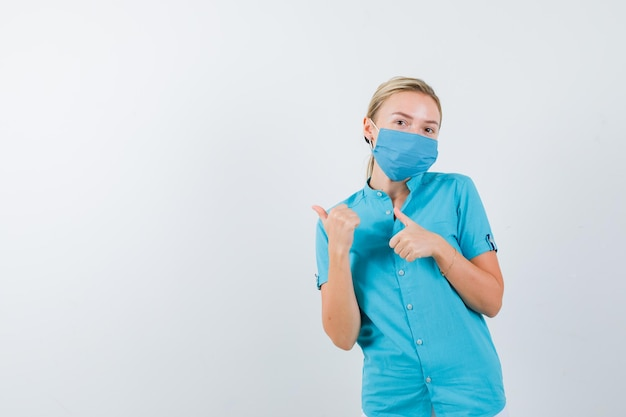 Jovem médica apontando para o lado direito com os polegares de uniforme e bonita