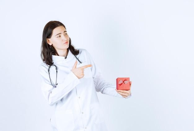 Jovem médica apontando seu lado esquerdo enquanto faz um sinal com a mão e segura seu presente na frente da parede vermelha