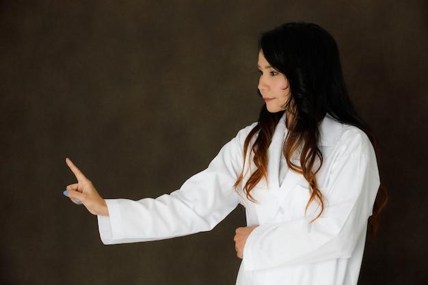 Jovem médica asiática com pose de estetoscópio parece tocar o botão de realidade virtual ou invisível em fundo cinza escuro