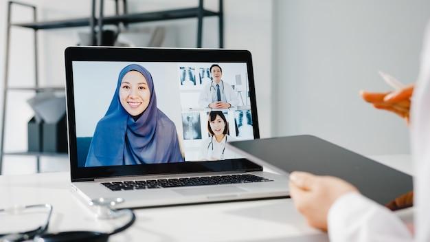 Jovem médica asiática em uniforme médico branco com estetoscópio usando computador, laptop, falando em videoconferência