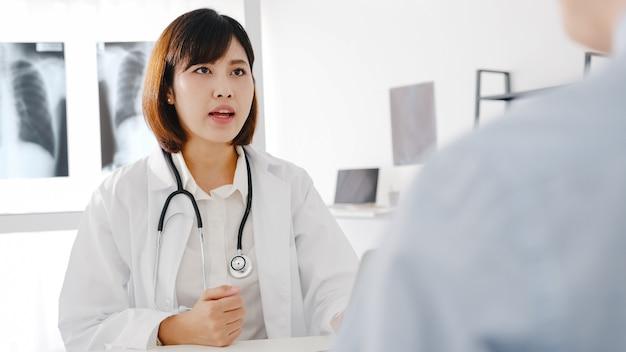 Jovem médica asiática em uniforme médico branco, usando um computador laptop, está dando uma ótima palestra para discutir os resultados