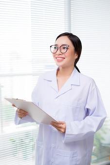 Jovem médica asiática segurando uma pasta no corredor do hospital