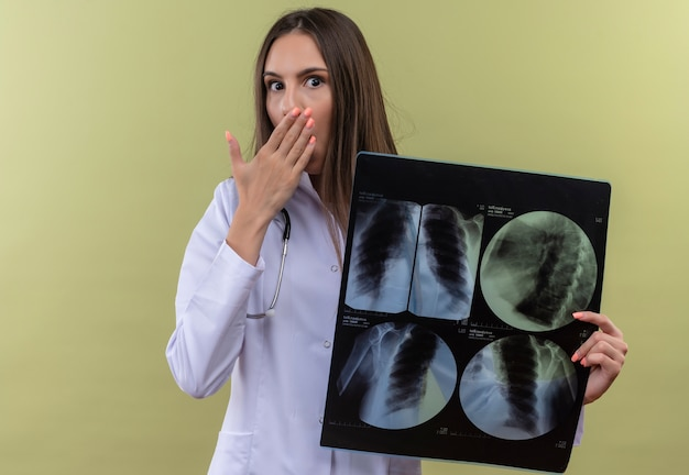 Jovem médica assustada usando uma bata médica com estetoscópio e segurando a boca coberta por raio-x sobre fundo verde