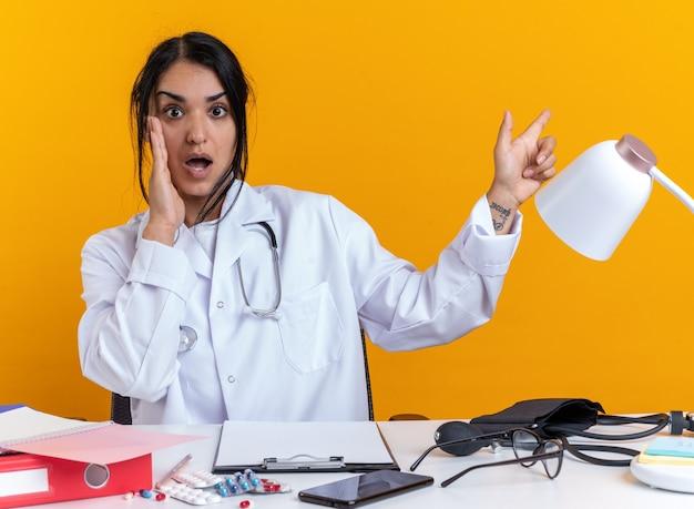 Jovem médica assustada, vestindo túnica médica com estetoscópio, se senta à mesa com pontos de ferramentas médicas ao lado, isolados em um fundo amarelo com espaço de cópia