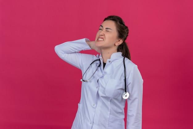Jovem médica cansada usando bata médica e estetoscópio colocou a mão no pescoço sobre fundo vermelho isoleted