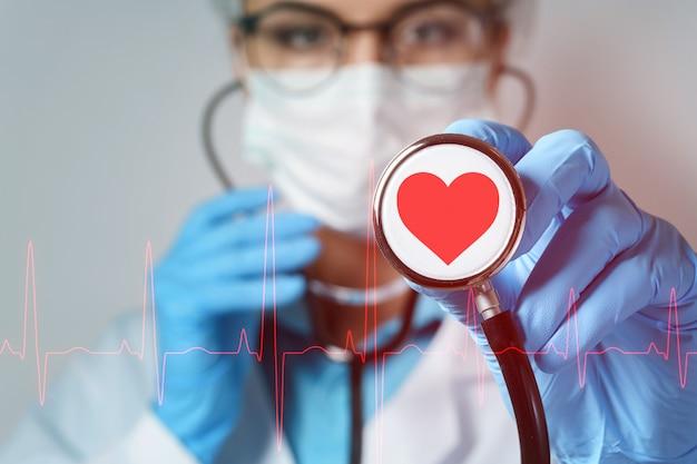 Jovem médica cardiologista com um estetoscópio verificando seus batimentos cardíacos